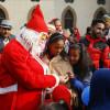 Santa Claus distributes gifts among children who had assembled at Holy Family Catholic Chrch…