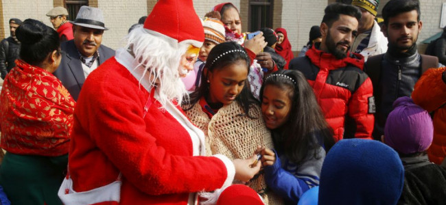 Santa Claus distributes gifts among children who had assembled at Holy Family Catholic Chrch...