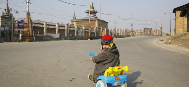 In the wake of strike and restrictions, this child tries his toy cycle skills on the deserted road...