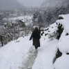 A pedestrian walks on snow covered Ferozpora link road near Tangmarg…