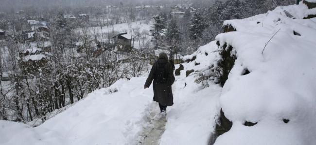 A pedestrian walks on snow covered Ferozpora link road near Tangmarg...