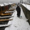 With Shikaras parked in a row, a boatman attempts to clear the path on Dal Lake…