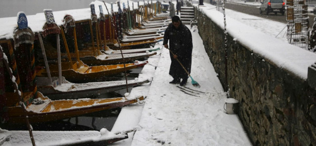With Shikaras parked in a row, a boatman attempts to clear the path on Dal Lake...
