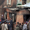 Locals throng the residential houses, damaged in Monday's encounter...