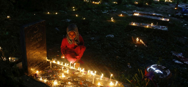 A child lit candles on the grave of her mother in a Srinagar graveyard on the auspicious ...