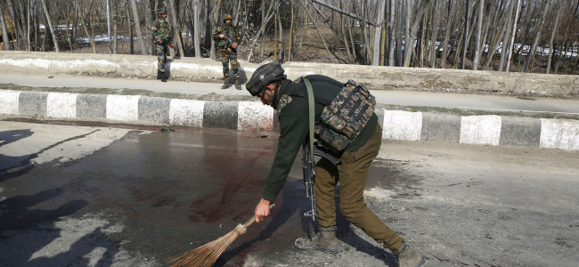 A policeman washes the blood stains from the encounter site...